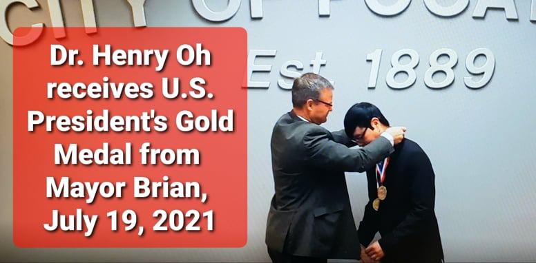 Dr. Henry Oh receives medal from Mayor Brian