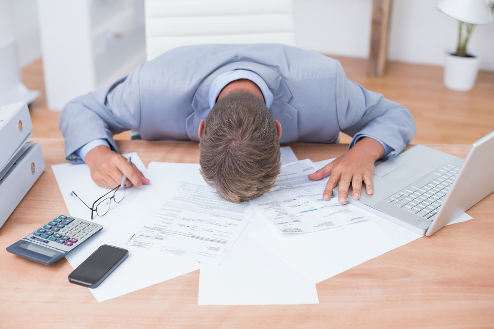 Businessman being depressed by accounting in his office
