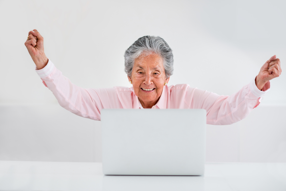 Elder woman celebrating her online success with arms up