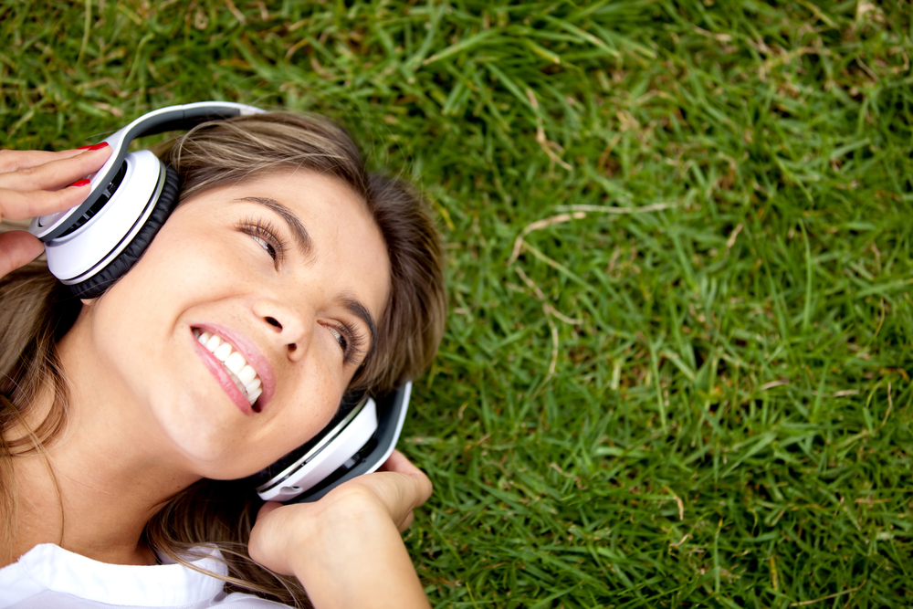 Girl listening to music at the park with headphones