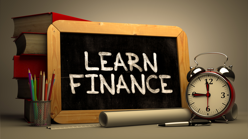 Handwritten Learn Finance on a Chalkboard. Composition with Chalkboard and Stack of Books, Alarm Clock and Rolls of Paper on Blurred Background. Toned Image.
