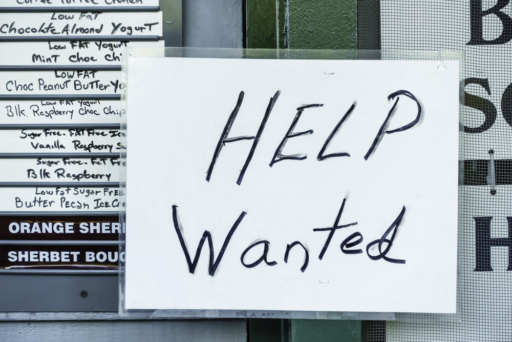 Laminated handwritten Help Wanted sign in window of ice cream and yogurt shop in tourist town