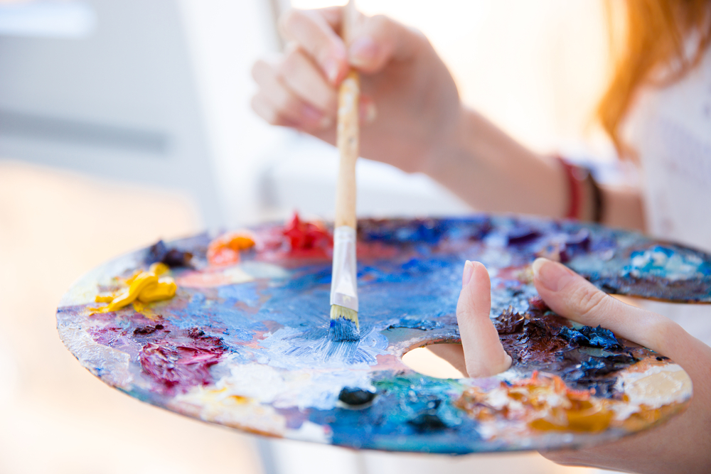 Closeup of paintbrush in woman hands mixing paints on palette-1
